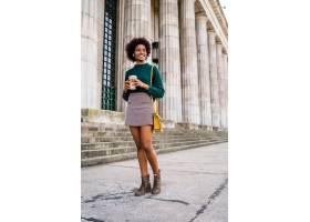黑人女商人在街上户外散步时拿着一杯咖啡的_12682421