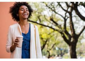 黑人女商人站在户外街道上微笑着拿着一杯_12740347