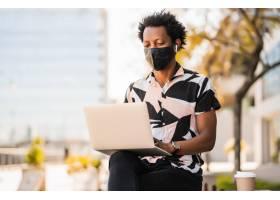 黑人旅游者坐在户外时使用笔记本电脑戴着_12830312