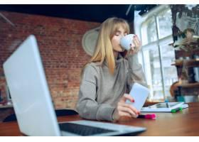美丽的高加索女商人拿着笔记本电脑在办公室_11877141