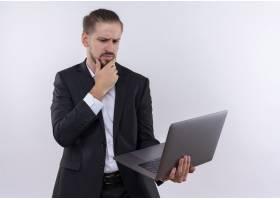 英俊的商务人士穿着西装拿着笔记本电脑_12525492