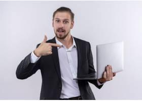 英俊的商务人士穿着西装拿着笔记本电脑_12526146