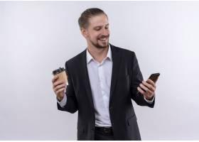 英俊的商务男士穿着西装手持智能手机和咖_12525511