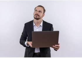 英俊的商务男士穿着西装手持笔记本电脑_12525498