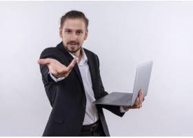 英俊的商务男士穿着西装手持笔记本电脑_12525509