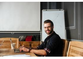 英俊的年轻人一边工作一边坐在咖啡旁_8073021