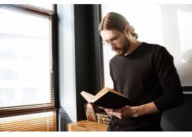 英俊的年轻人在办公室边工作边看书_8076274
