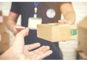 送货员微笑着拿着一个纸箱_4334594