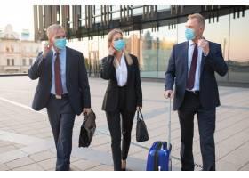 戴口罩的商务游客带着公文包或手提箱旅行_9648944