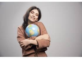 深色头发的女子在灰色上拥抱地球仪_13083830