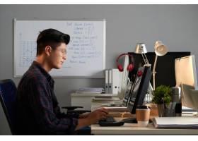 戴眼镜的年轻亚裔男子在办公室用电脑工作的_5576673