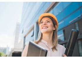 戴着黄色头盔站在户外的职业建筑师女性肖像_9882682