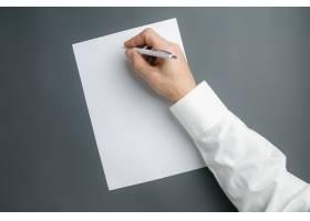 男性手持钢笔在灰色墙上的空白纸上书写文_12786648