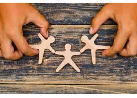 木质背景平铺上的营销理念双手触摸木质人_9178660