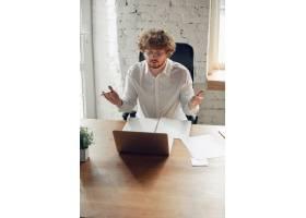 穿着商务服装的高加索年轻人在办公室工作_13348900