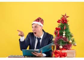 正面怒气冲冲的商人对坐在圣诞树附近桌子旁_13361389