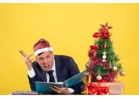 正面怒气冲冲的商人戴着圣诞帽坐在圣诞树_13361387