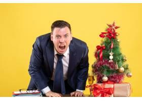 正面怒气冲冲的商人站在圣诞树附近在黄色_13361383