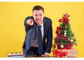 正面怒气冲冲的商人站在圣诞树附近的桌子后_13361381