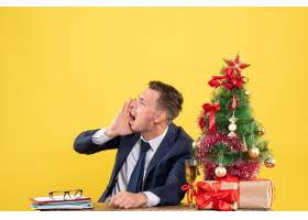 正面怒气冲冲的男子打电话给坐在圣诞树旁的_13361392