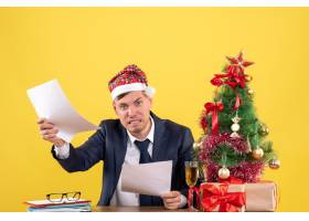 正面看戴着圣诞帽的愤怒男子坐在圣诞树附_13361493