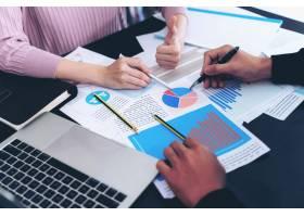 紧贴在办公桌前忙于笔记本和文件工作的商务_5389008