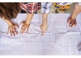 工人们在主体平面图上谈论建筑工程_13250926