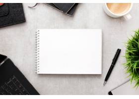 工作区上装有办公用品的空白记事本或笔记本_9076689