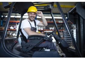 工厂仓库里微笑的专业叉车司机的肖像_11036105