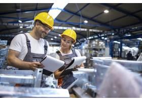 工厂工人在大工业大厅分析生产结果_11034297