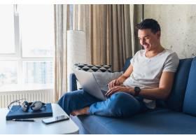 年轻漂亮的男人坐在家里的沙发上上网玩笔记_9699549