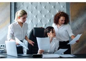 年轻的商界女性董事坐在办公桌前使用笔记_9946033
