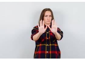 年轻的女士穿着休闲衬衫摆出停下来的手势_13298530