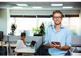 年轻英俊的成功商人微笑着手持平板电脑_7590512