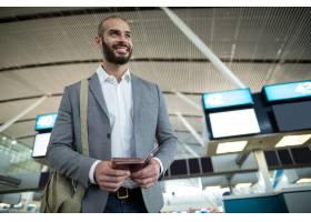 微笑的商人拿着登机牌和护照_10747909