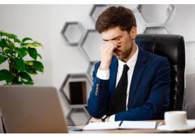 心烦意乱的年轻商人坐在工作场所办公室背_7857703