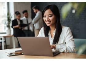 快乐的年轻亚洲女商人使用笔记本电脑_6514536