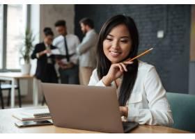 快乐的年轻亚洲女商人使用笔记本电脑_6514538