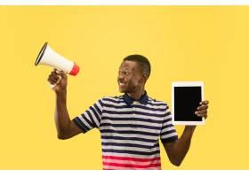 快乐的年轻非裔美国人在黄色的工作室背景_13455968
