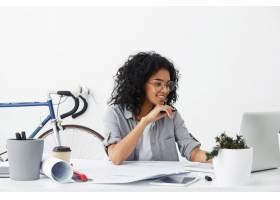 快乐的漂亮女工程师坐在办公室内部拿着文件_10273027
