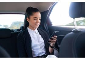 商务女性在开车上班的路上使用手机的肖像_12682357