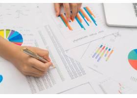 商界女性手持财务图表和笔记本电脑放在标签_1018847