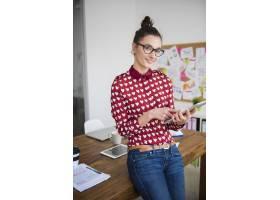 在办公室使用数字平板电脑的年轻女子_12751699