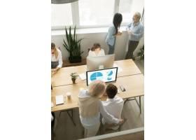在办公室工作的高级和年轻员工俯视垂直视_3954487