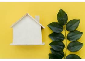 在黄色背景下靠近绿叶的木制房屋模型_3725031