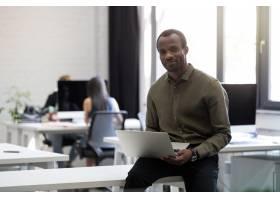 坐在办公桌上的快乐的非洲裔美国商人微笑着_7337477