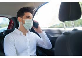 在开车上班的路上戴着口罩打电话的商人的_12955284