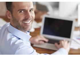 在电脑上工作时快乐的男人转过身来微笑着_13274188