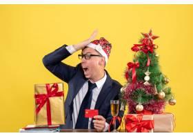 坐在圣诞树旁的桌子前一位男子把手放在额_13361358
