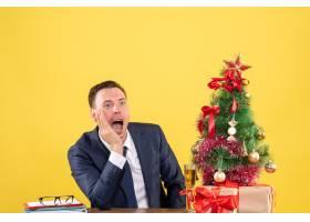 坐在圣诞树旁的桌子旁黄色背景上出现的前_13361365